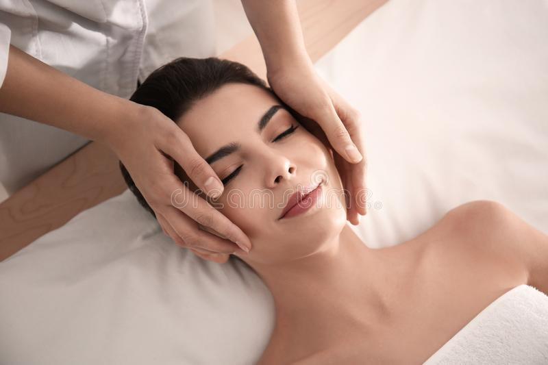 Young woman enjoying facial massage in spa salon stock photos