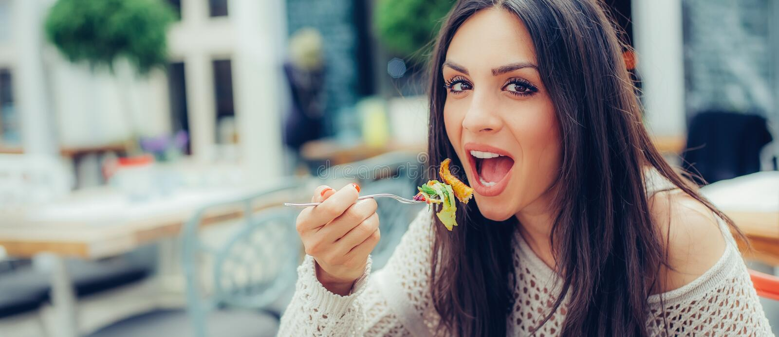 Young woman enjoying food in a restaurant, having her lunch break royalty free stock photos
