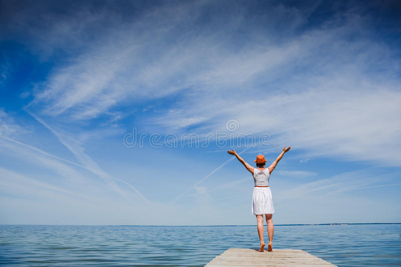 Young woman enjoying freedom at the beach. Young woman in white dress and hat enjoying summer at the beach stock image