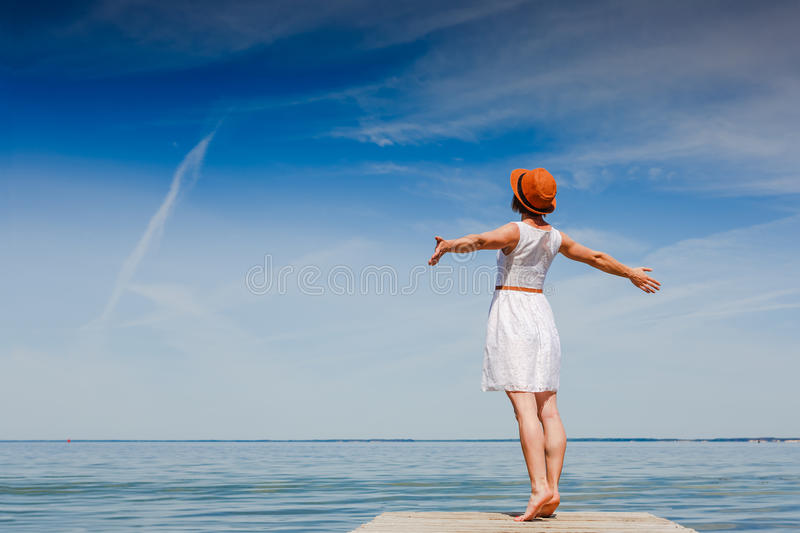 Young woman enjoying freedom at the beach. Young woman in white dress and hat enjoying summer at the beach stock photography