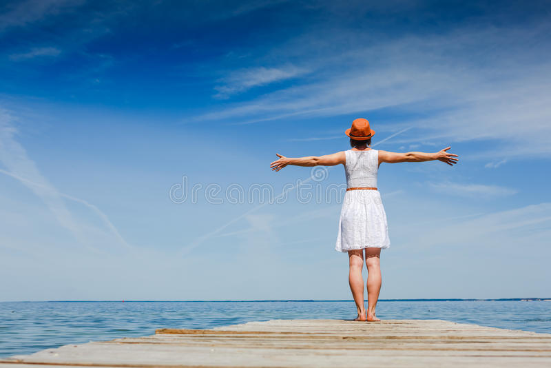 Young woman enjoying freedom at the beach. Young woman in white dress and hat enjoying summer at the beach stock photos