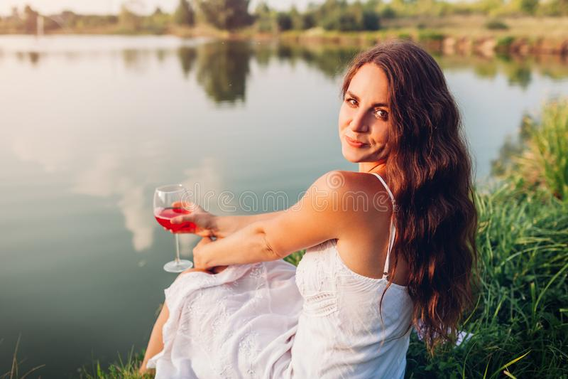 Young woman enjoying glass of wine on river bank at sunset. Woman admiring landscape while having drink stock photography