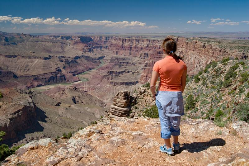 Young woman enjoying Grand Canyon view from Desert View. Young woman enjoys remarkable view of Grand Canyon from Desert View on South Rim, Grand Canyon National stock photo