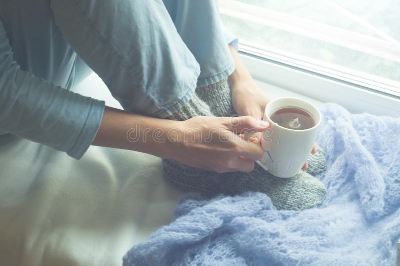 Young Woman Enjoying her morning coffee or tea, Looking Out the Window. Beautiful romantic unrecognizable girl drinking hot drink royalty free stock photography