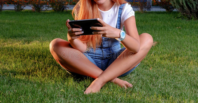 Young woman enjoying her time in park with tablet. Teen girl issitting crosslegged on spring grass with her digital tablet PC in arms. Young woman enjoying her royalty free stock photo