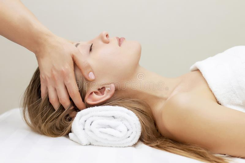 Young woman enjoying massage in spa salon. beautiful girl on a head and face massage procedure lies on white. stock photography
