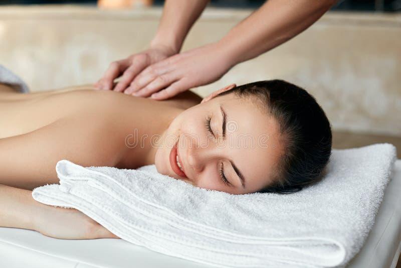 Young woman enjoying massage in spa salon. Body care. Woman having massage stock image