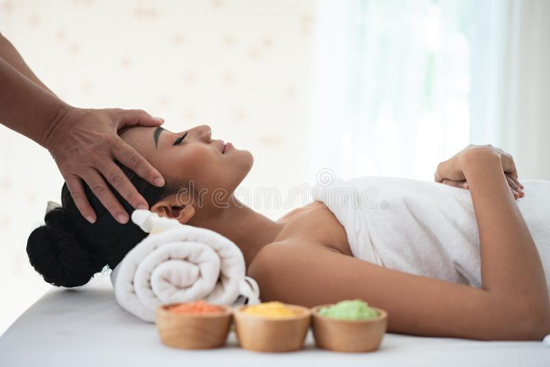 Young woman enjoying massage in spa salon royalty free stock photo