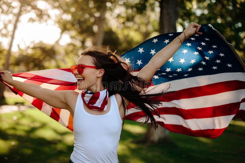 American woman with national flag at park royalty free stock images