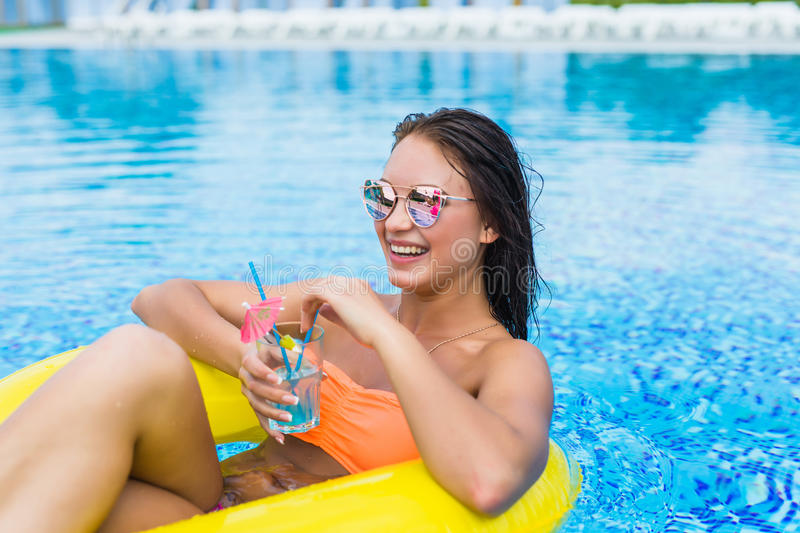 Young woman enjoying with rubber ring and cocktail in swimming pool. At summertime royalty free stock image