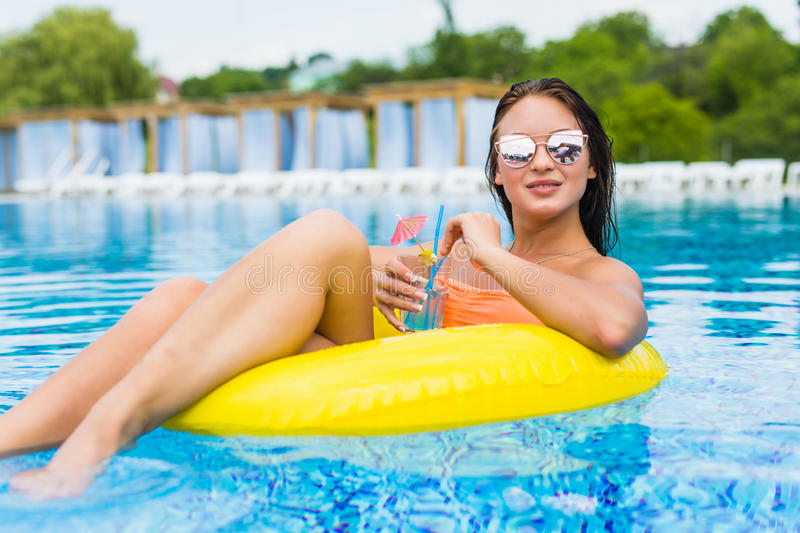 Young woman enjoying with rubber ring and cocktail in swimming pool. At summertime stock photo