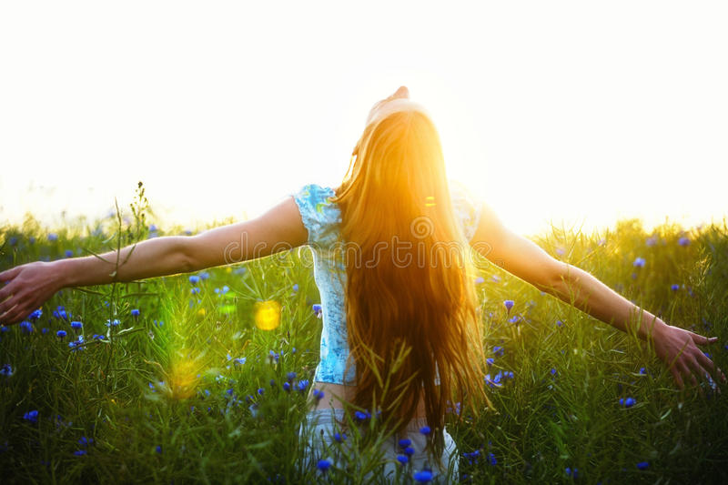 Young woman enjoying sunlight with raised arms in canola field stock photo