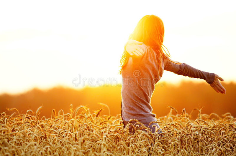 Young woman enjoying sunlight with raised arms in straw field stock photos