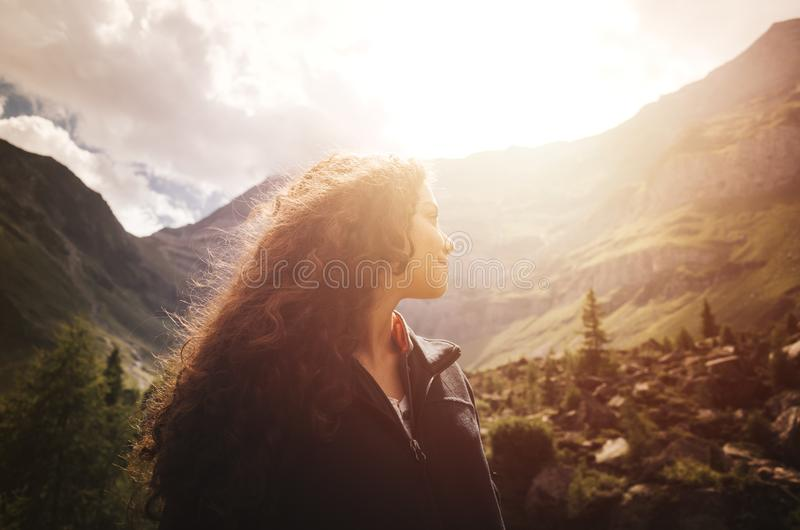 Young woman enjoying the sunset in the dolomite mountains in Northern Italy stock photo