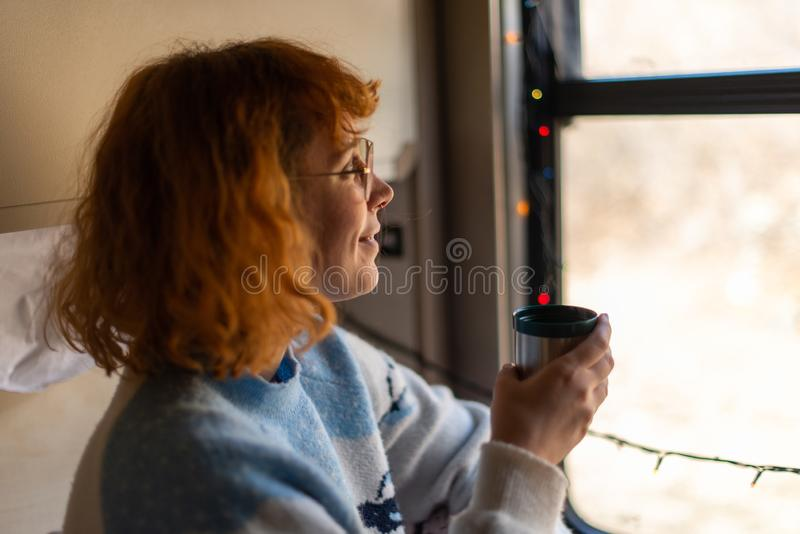 Young woman enjoying traveling with train, drinking coffee and watching outside of the window. lying down in her compartment. stock photography