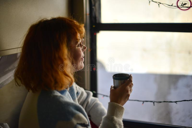 Young woman enjoying traveling with train, drinking coffee and watching outside of the window. lying down in her compartment. royalty free stock photography