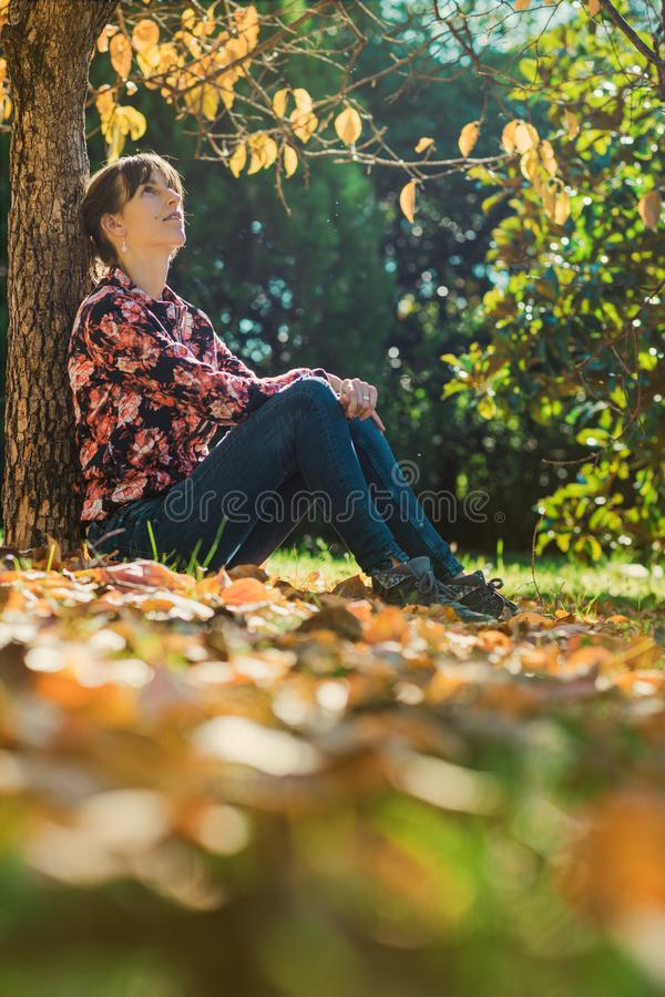 Young woman enjoying under an autumn tree stock image