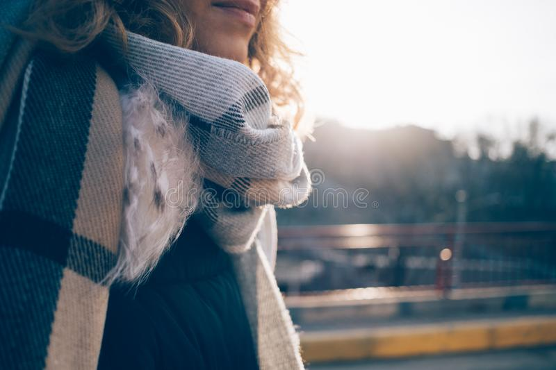Young woman enjoying a walk in the city. At cold sunny weather. Close-up cropped photo of happy girl in warm scarf. Shining sun and blurred city street on the royalty free stock photography