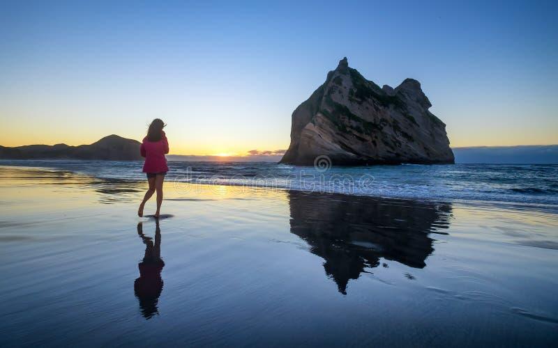 Young woman enjoys wharariki beach in New Zealand. Young woman enjoys beautiful wharariki beach in New Zealand. Sunset image of girl on beach stock photos