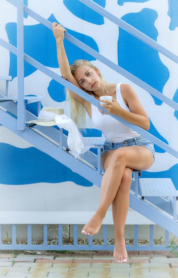 Young woman enjoys a cup of coffee. On the stairs royalty free stock photos