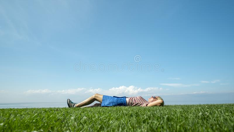 A young woman enjoys warmth and summer, lying on the green grass against the blue sky royalty free stock images