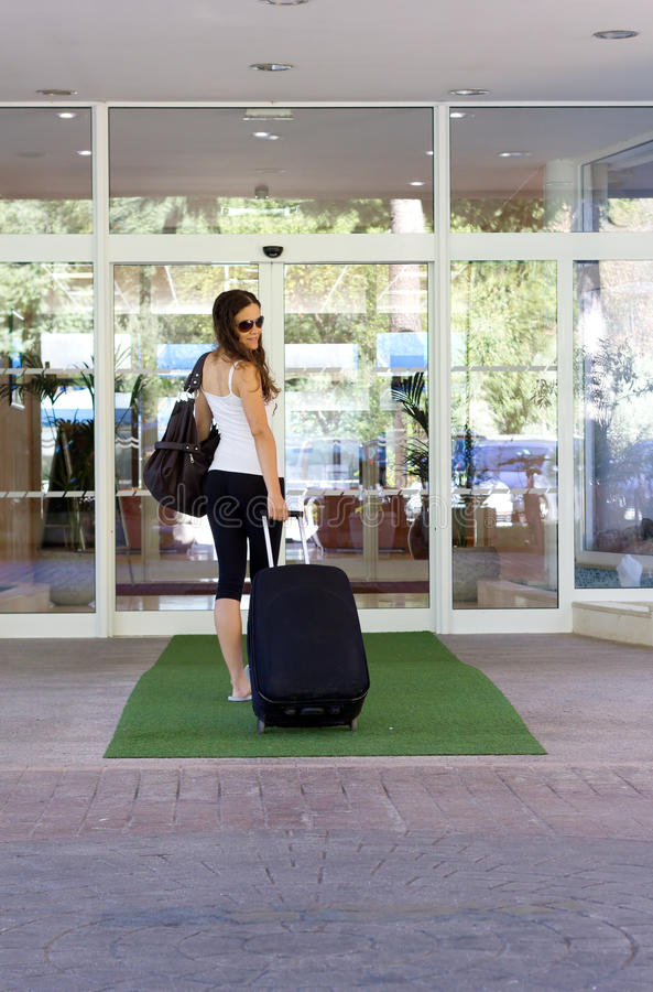 Young woman entering hotel royalty free stock photography