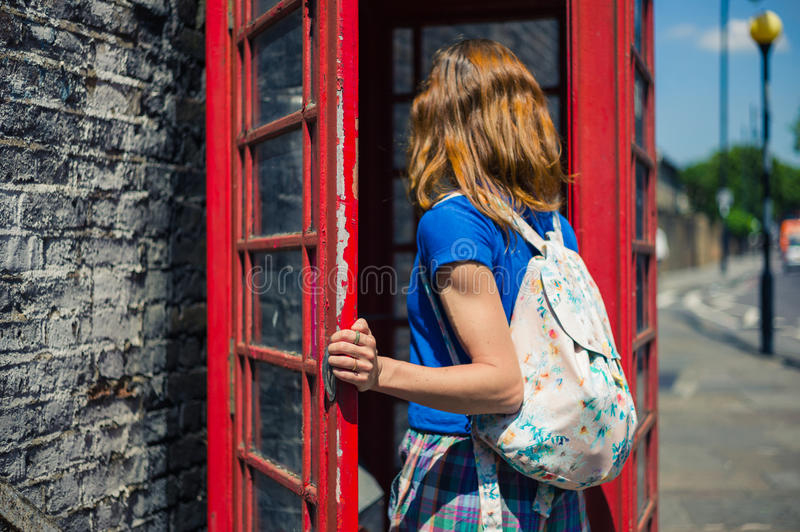 Young woman entering a phone booth stock image