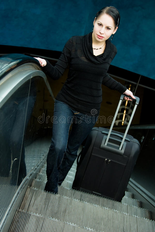 Young Woman On Escalator. Holding her luggage stock photography