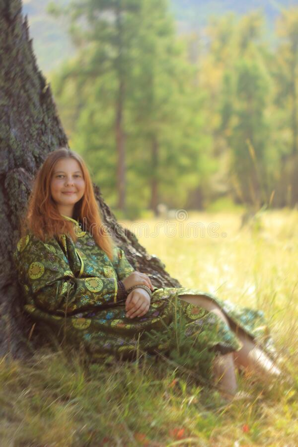 A young woman of European appearance with red hair in the traditional nomadic clothes of Mongolia and Tuva - a dressing gown in royalty free stock photography