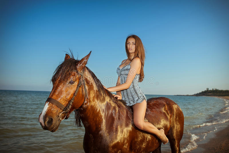 Young woman evening beach horse ride. Carefree young woman evening beach horse ride royalty free stock photo