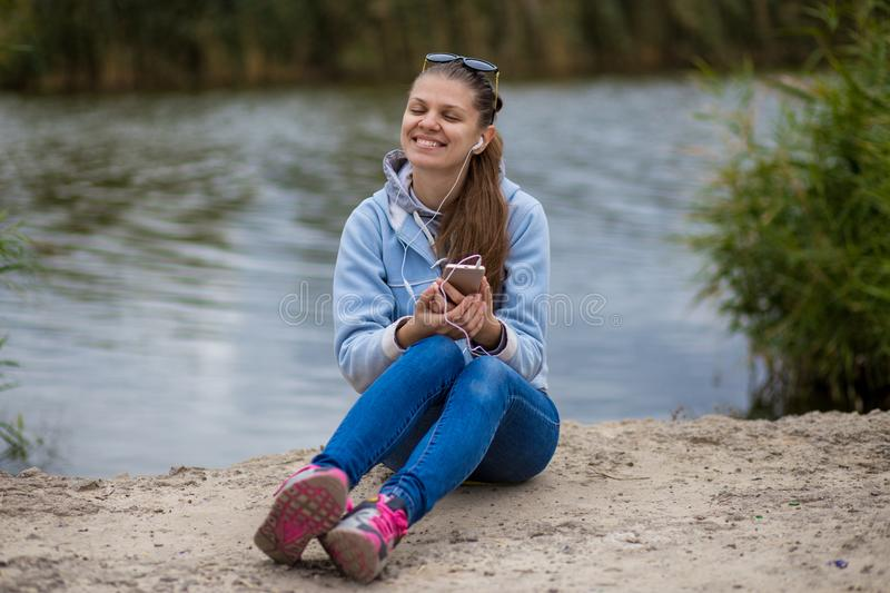 Young smiling woman in excellent spirits with a phone and listens to music royalty free stock image