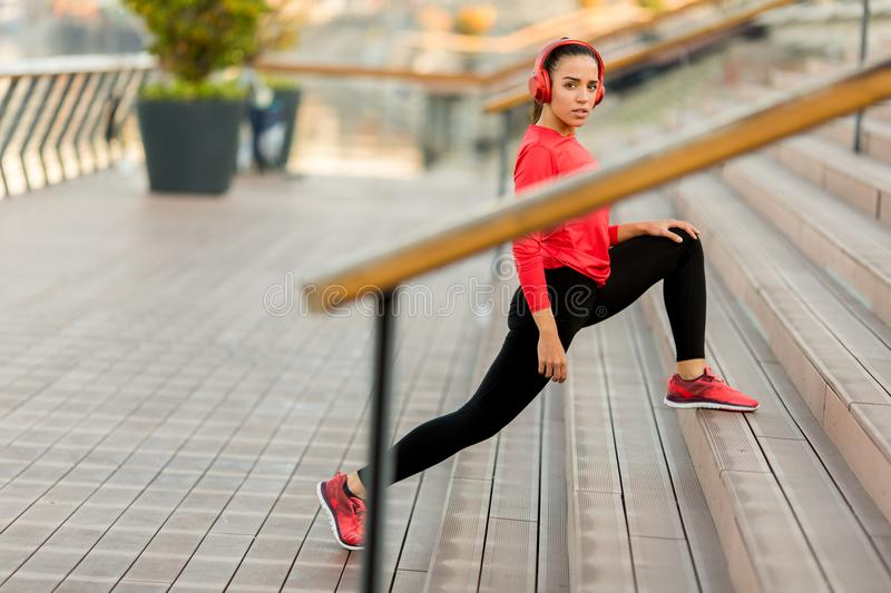 Young woman exercice outdoor. On stairs royalty free stock photo