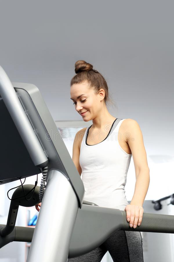 A young woman in an exercise room is running on an automatic treadmill. royalty free stock photography