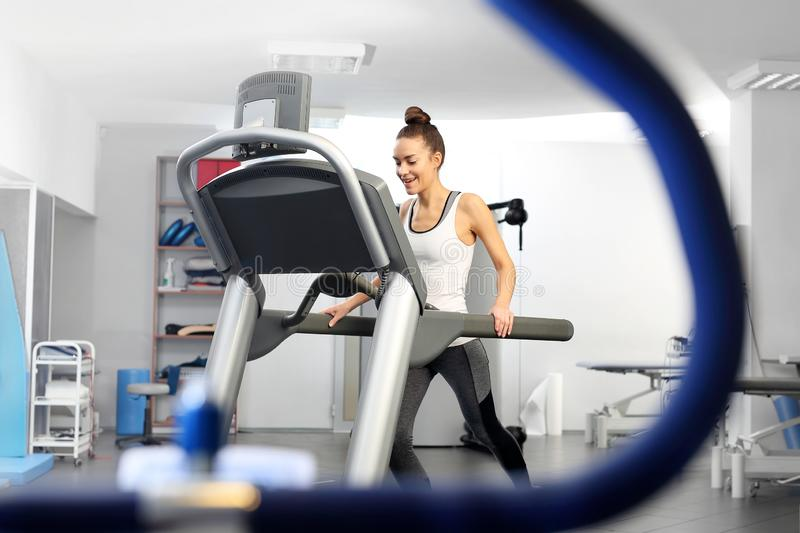 A young woman in an exercise room is running on an automatic treadmill. royalty free stock image