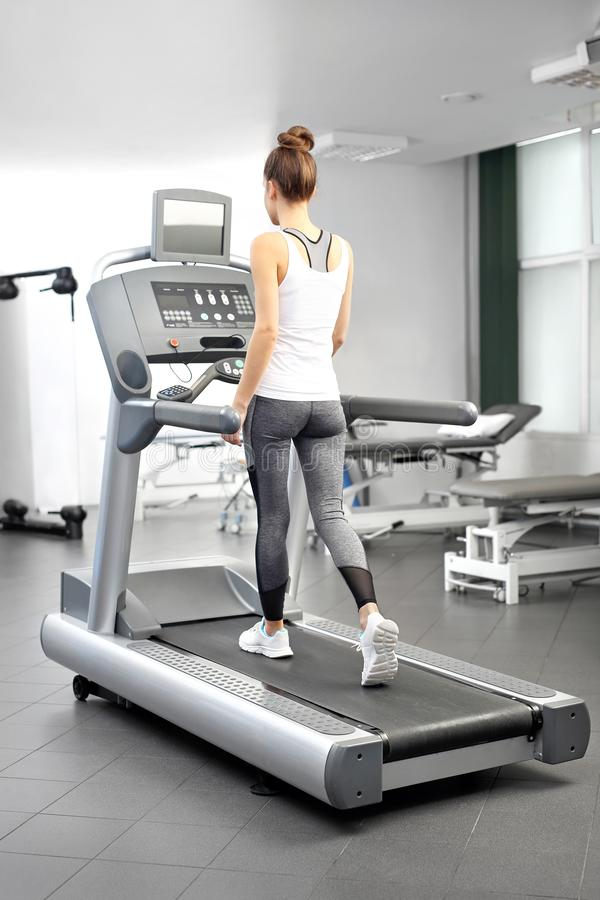 A young woman in an exercise room is running on an automatic treadmill. stock photos