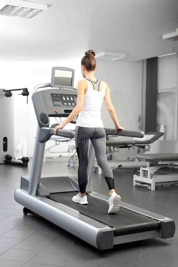A young woman in an exercise room is running on an automatic treadmill. stock image