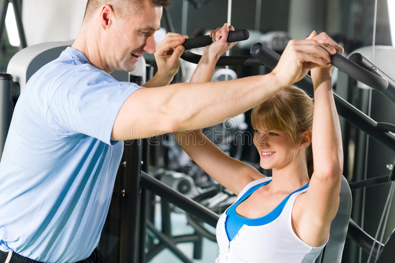 Young woman exercise on shoulder press machine. Young women exercise on shoulder press machine with personal trainer royalty free stock photography