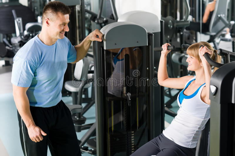 Young woman exercise on shoulder press machine. Young women exercise on shoulder press machine with personal trainer stock photos