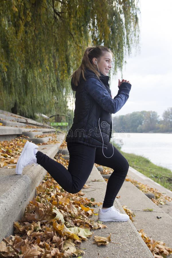 Young woman exercises by the river. Selective focus and small depth of field, lens flare royalty free stock photos