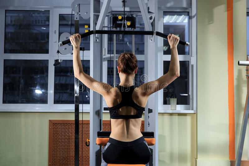 Young Woman Exercising Back On Machine In The Gym And Flexing Muscles - Muscular Athletic Bodybuilder Fitness Model stock photography