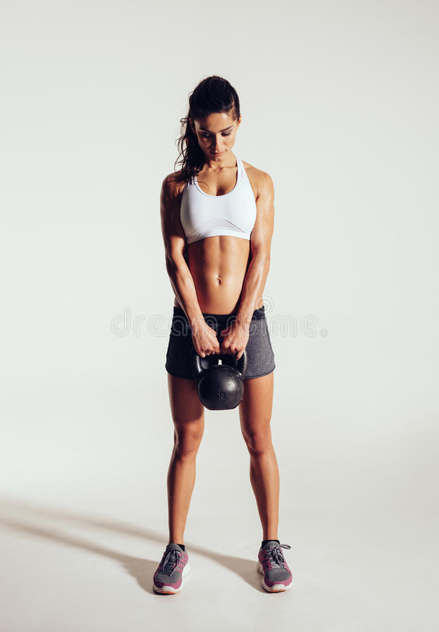 Young woman exercising crossfit with kettle bell. Pretty young woman exercising crossfit with kettle bell weight. Crossfit female working out on grey background stock image