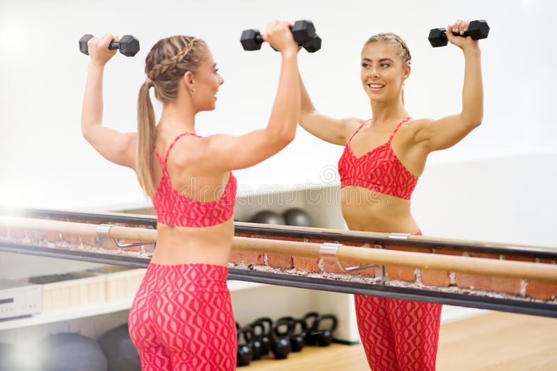 Young woman exercising with dumbells at gym stock image