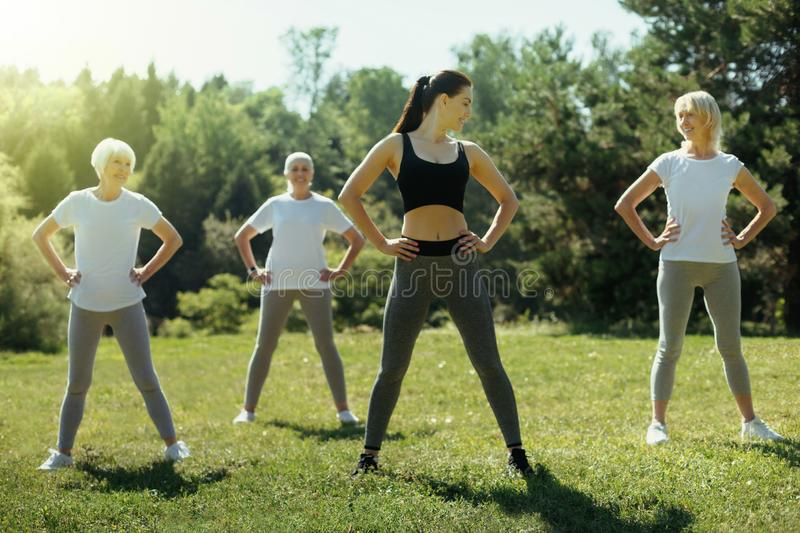 Young woman exercising with group of elderly people royalty free stock photo