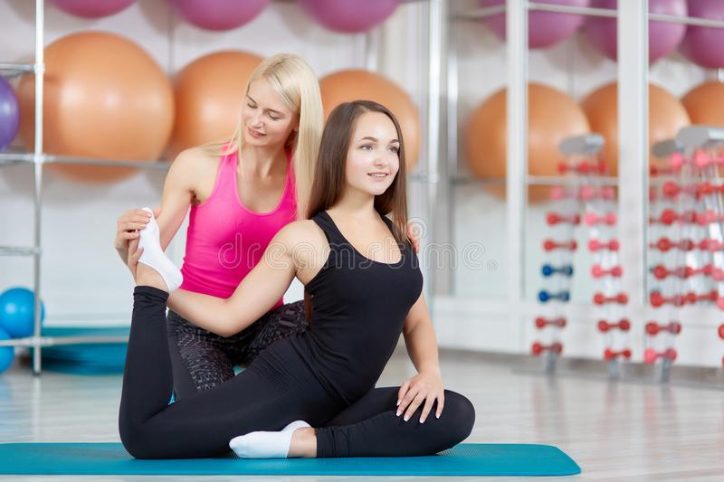 Young woman exercising with her fitness instructor stock photos
