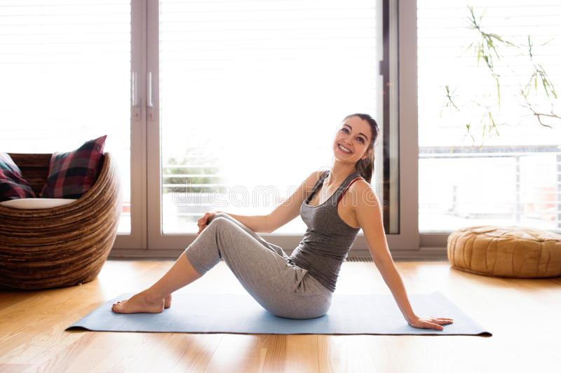 Young woman exercising at home on a mat royalty free stock photo