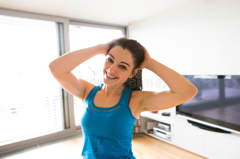 Young woman exercising at home, stretching neck. stock image