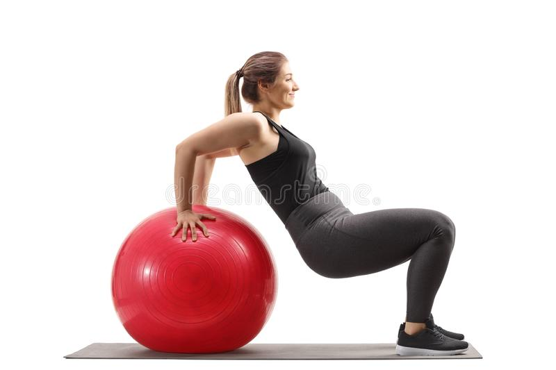 Young woman exercising sit ups with a fitness ball. Isolated on white background royalty free stock photos