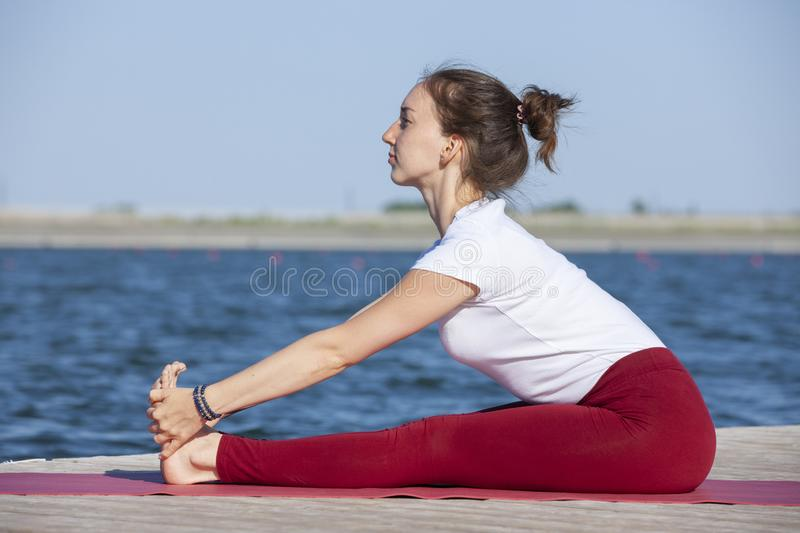 Young woman exercising yoga pose by the lake shore at sunset, girl in headstand yoga pose. People travel relaxation concept. Portrait royalty free stock photography