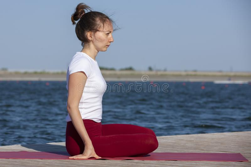Young woman exercising yoga pose by the lake shore at sunset, girl in headstand yoga pose. People travel relaxation concept. Portrait royalty free stock images