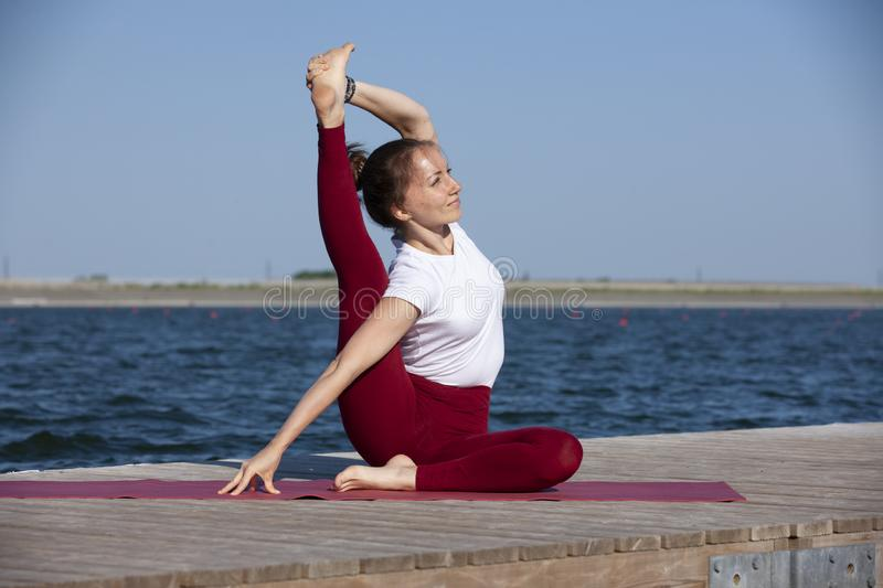 Young woman exercising yoga pose by the lake shore at sunset, girl in headstand yoga pose. People travel relaxation concept. Portrait royalty free stock photo
